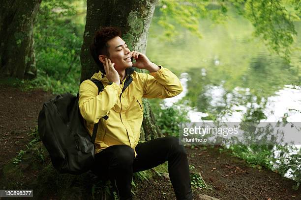 young man talking mobile phone in the forest
