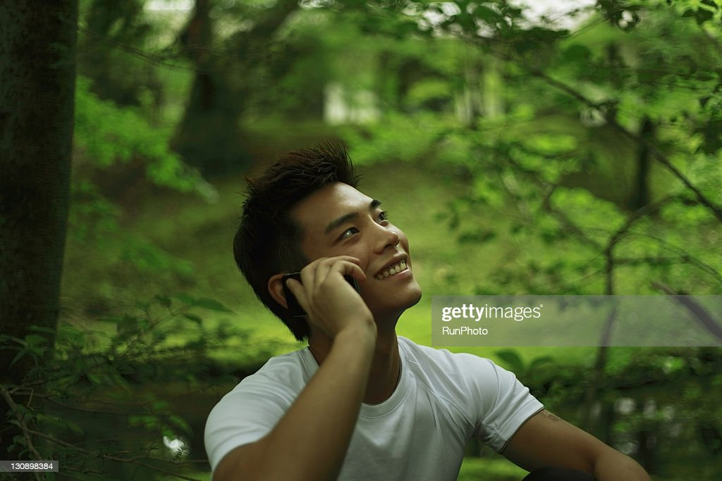 young man talking mobile phone in the forest : Stock Photo