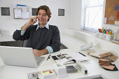 Young man talking on cell phone and using laptop at desk, laughing