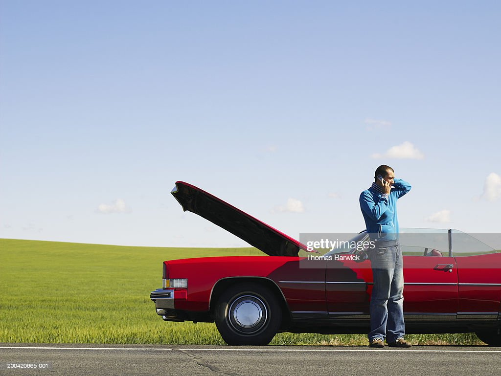 Young man talking on cell phone beside convertible with hood up