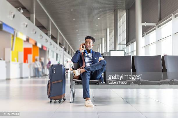 Young man talking on phone at airport lounge