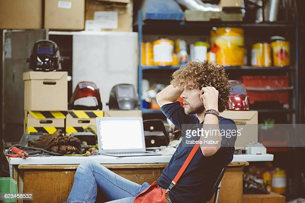 Young man talking on phone in a workshop