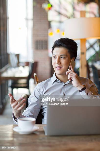 Young man talking on phone in cafe