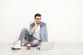 Young man talking on phone on floor with laptop. Busy man in glasses working and have coffee break. Communication concept