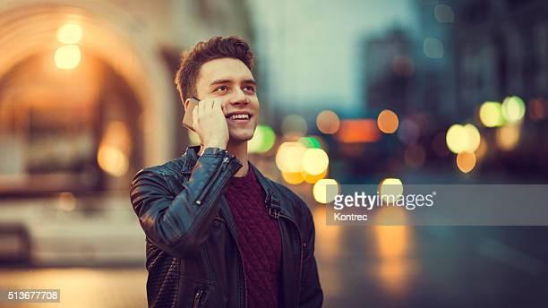 Jovem Homem a falar ao telefone ao ar livre, à noite