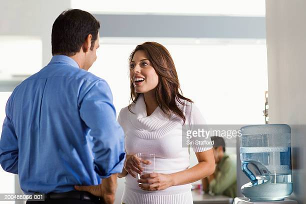 Young man talking to female colleague by watercooler