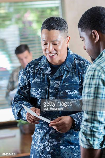Young man talking to military recruitment officer.