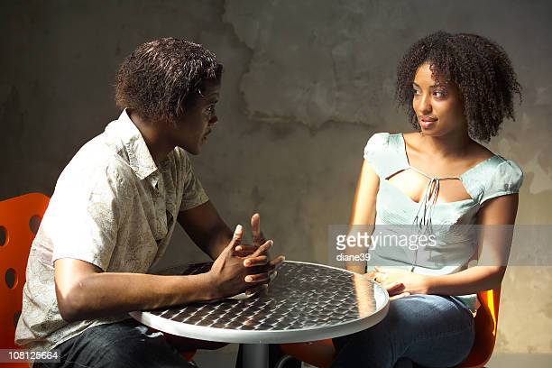 Young Man Talking with Woman and Sitting at Cafe Table