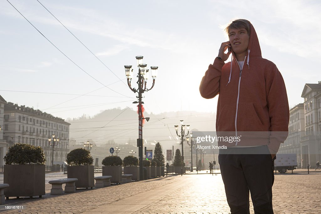 Young man talks on phone, in urban piazza : Stock Photo