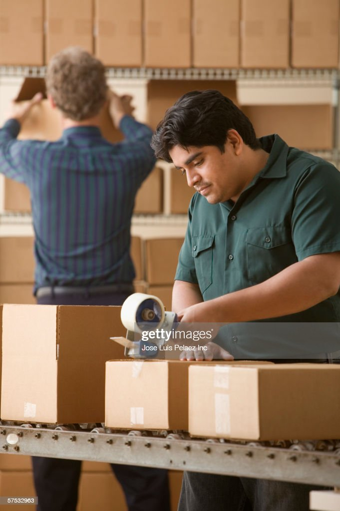 Young man taping a cardboard box closed : Stock Photo