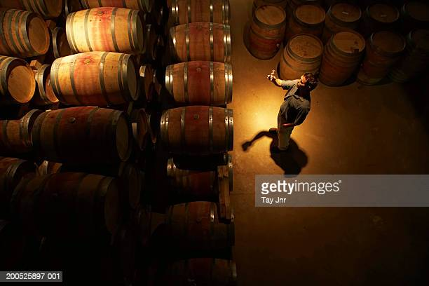 Young man tasting wine in cellar, overhead view