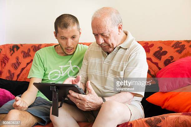 Young man teaching a old man how to use a tablet