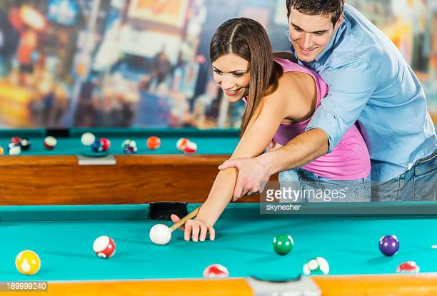 Young man teaching his girlfriend to play pool