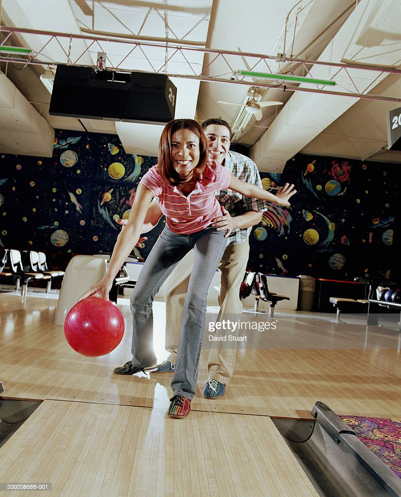Young man teaching young woman to bowl, smiling, in bowling alley
