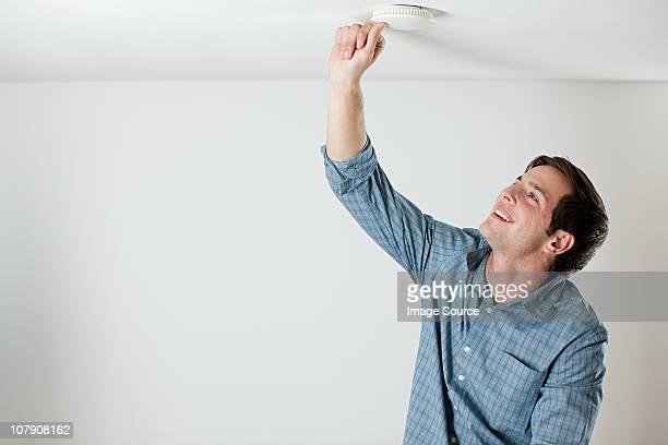 Jeune homme tests le détecteur de fumée au plafond
