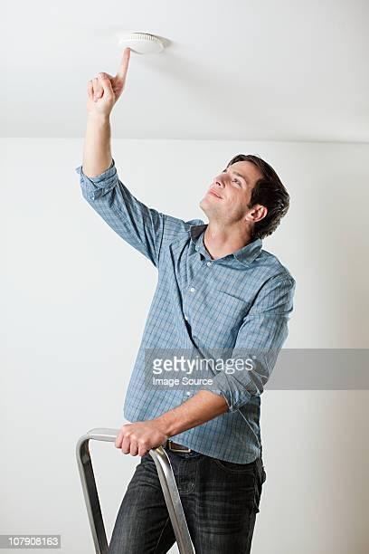 Young man testing smoke alarm on ceiling