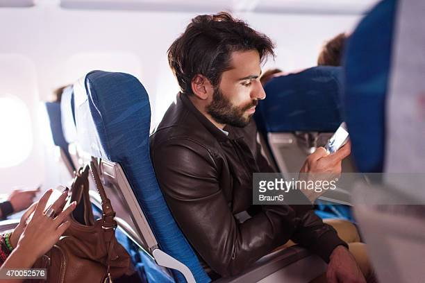 Young man text messaging on mobile phone in airplane.