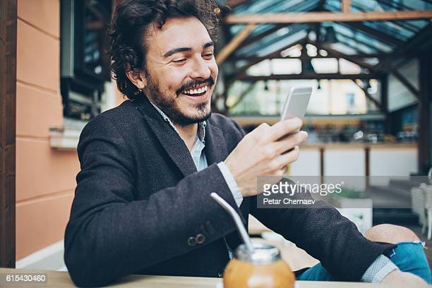 Young man texting in the restaurant