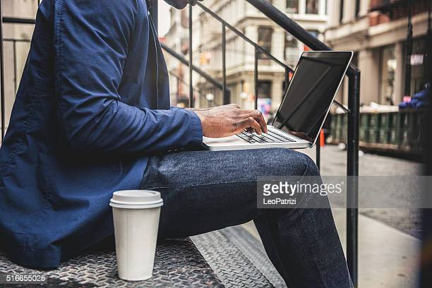 Young man texting on laptop