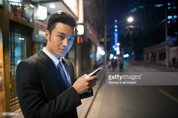 Young man texting on the street at night, China