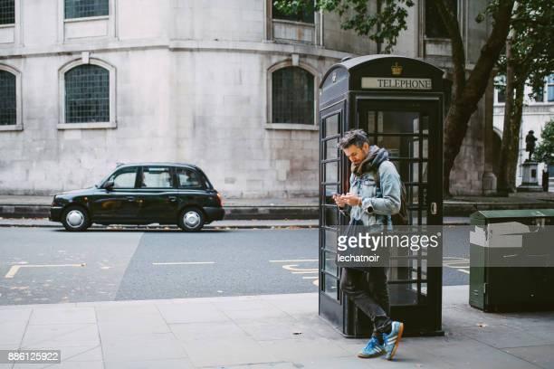 Junger Mann SMS stehen durch die Retro-Phonebooth auf der Straße in London