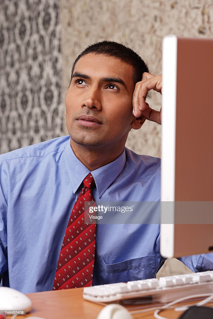 Young man thinking sitting in front of the computer : Stock Photo