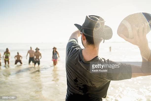 Young man throwing American football ball to friends in sea at Newport Beach, California, USA