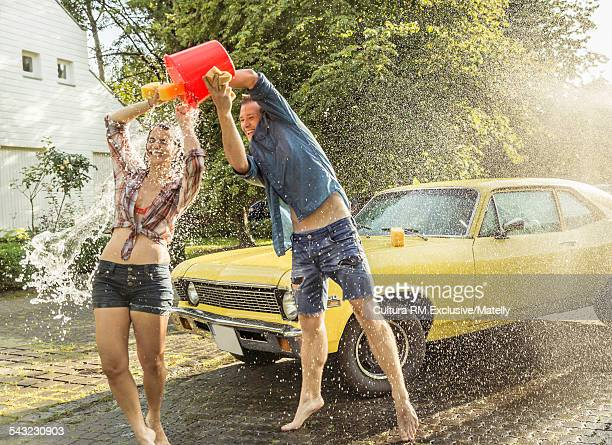 Young man throwing bucket of water over girlfriend whilst washing vintage car
