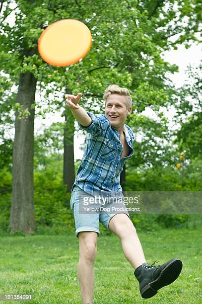Young man throwing Frisbee in park