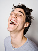 Young man throwing head back laughing, close-up