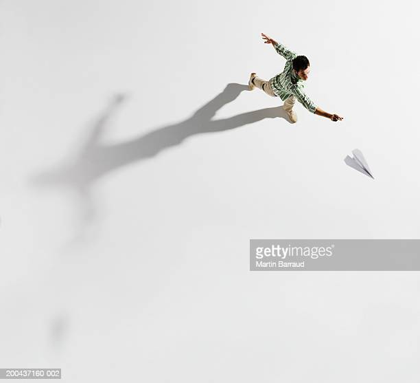 Young man throwing paper aeroplane, overhead view