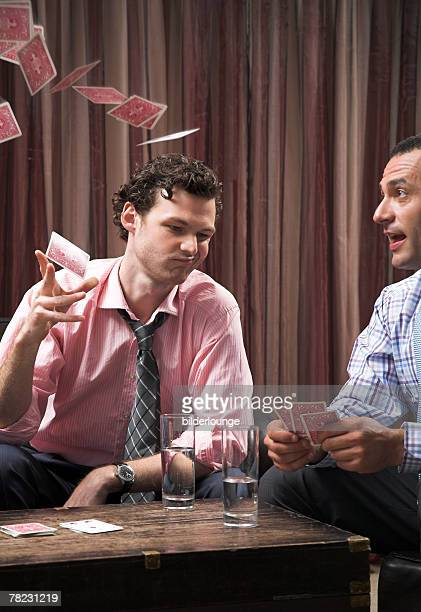 young man throwing playing cards in the air out of frustration
