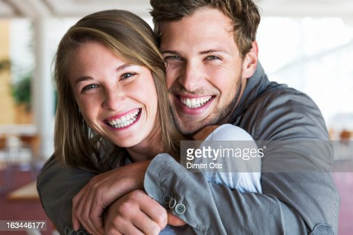 Young man tightly embracing his girlfriend