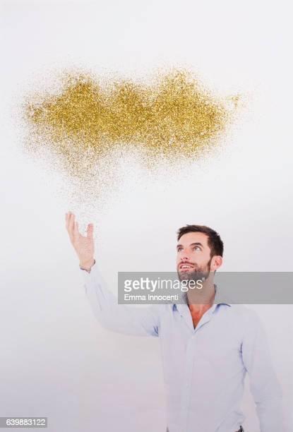 Young man touching a golden cloud