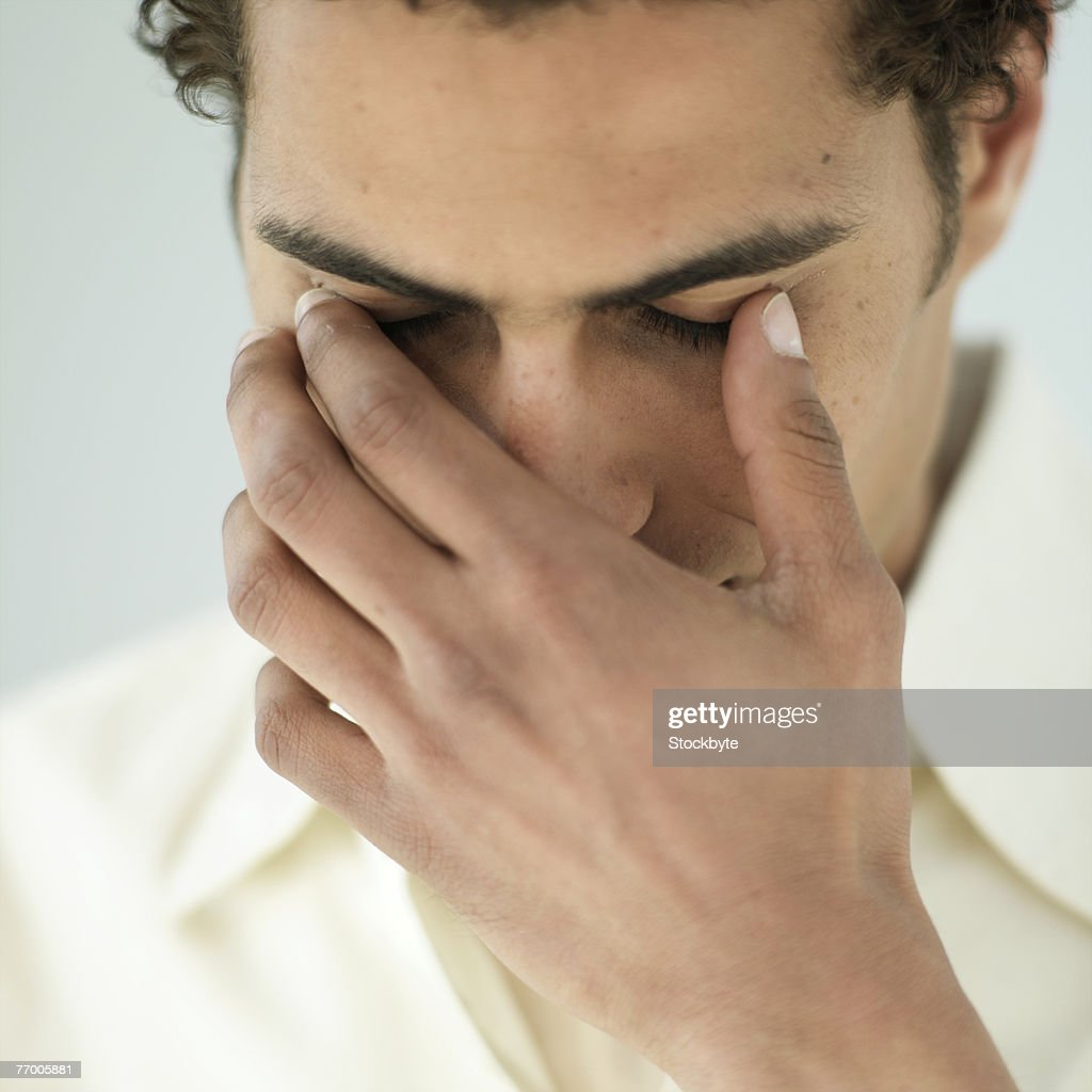 Young man touching closed eyes with fingers, close-up : Stock Photo