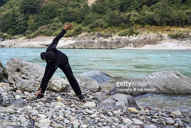 Young Man Touching Toe Exercise at Riverside of Ganga, Rishikesh