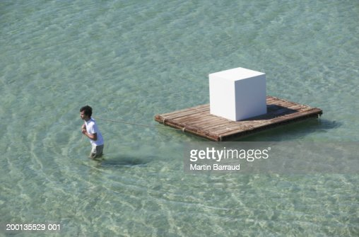 Young man towing large white cube on raft, elevated view