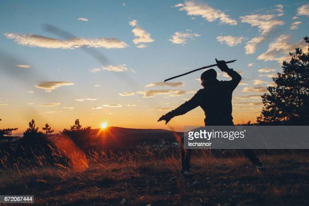 Young man training martial arts in the nature