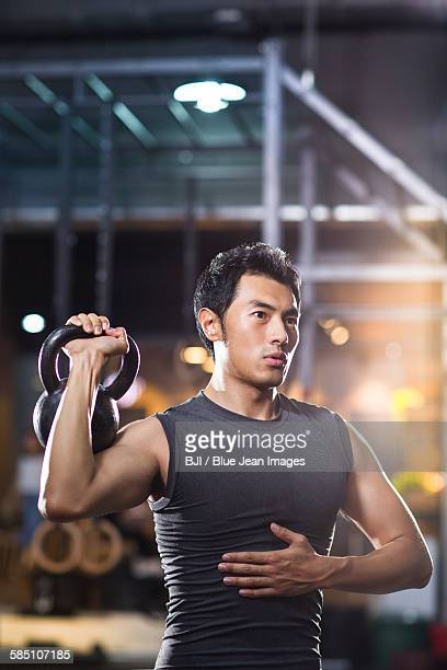 Young man training with kettlebell in gym gym