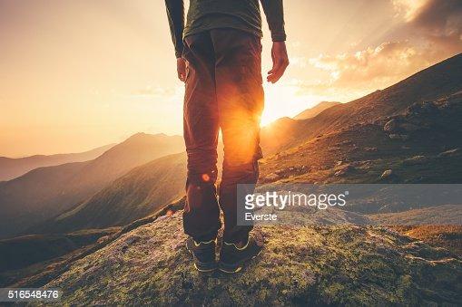 Jovem viajante pés em pé com pôr do sol montanhas : Foto de stock