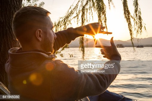 Young man traveling in China makes natural finger frame