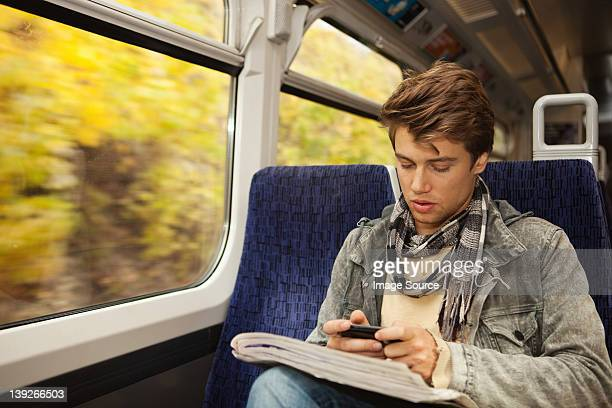 Young man travelling on train using cellphone