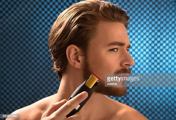 Young man trimming his beard.