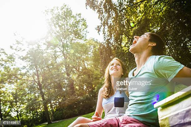 Young man trying to catch grape in his mouth, sitting with girlfriend in park