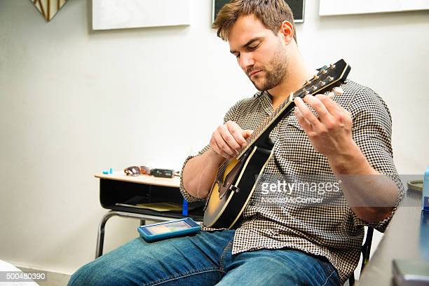 Young man tuning his mandolin using moble phone app