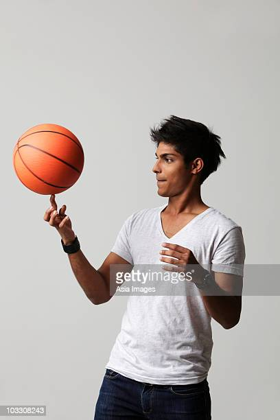 young man twirling basket ball on his finger