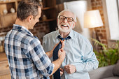 Sonly care. Pleasant young man tying the tie of his elderly father while the man laughing, closing his eyes
