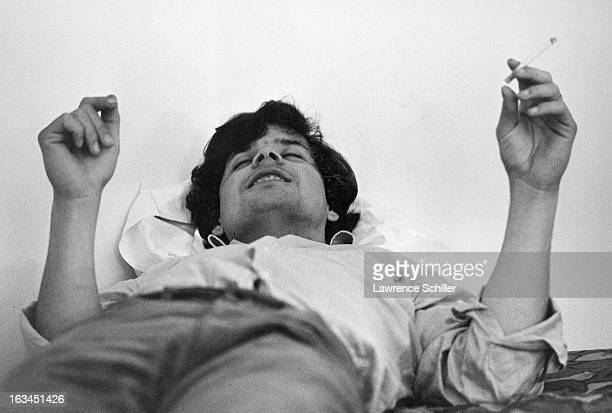 A young man under the influence of LSD lies on the floor with a cigarette in one hand Los Angeles California 1966