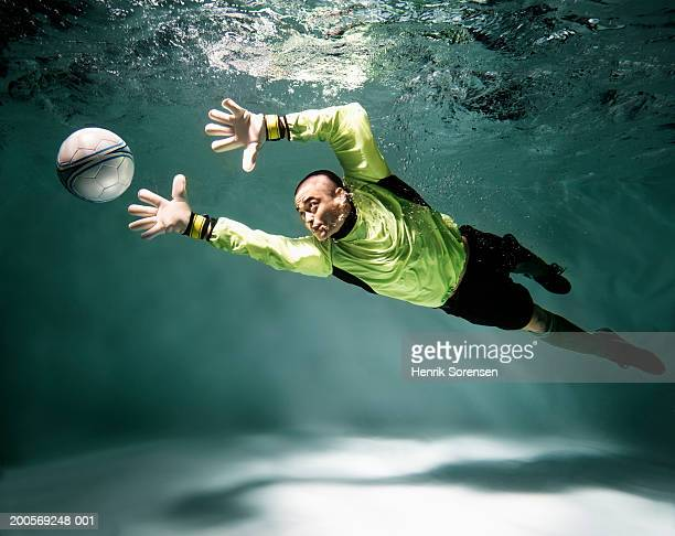 Young man underwater playing football