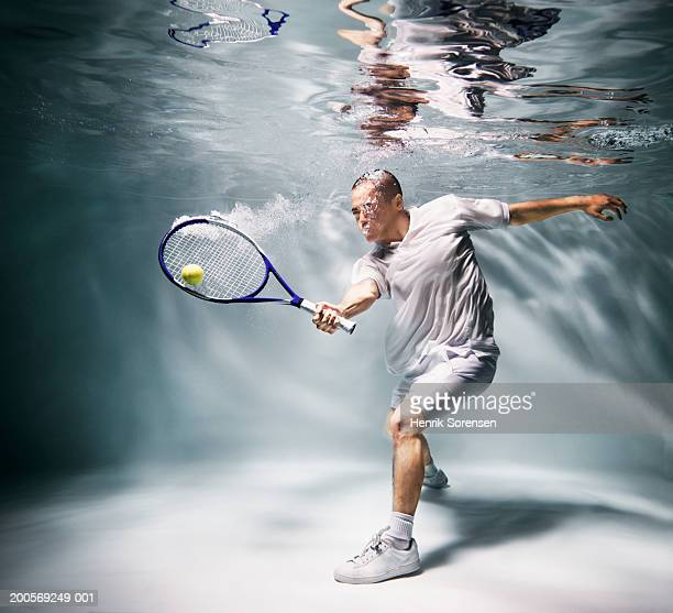 Young man underwater playing tennis